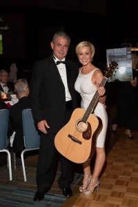 Kellie Pickler poses with Frank Stewart, who won her signed guitar during the Live Auction at the USO of North Carolina's Ninth Annual Salute to Freedom Gala in Raleigh, N.C. on Oct. 19.  Stewart's winning bid for the guitar was $4,900. Photographer: Jess Isaiah Levin
